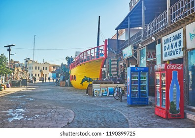 DAHAB, EGYPT - DECEMBER 25, 2017: The wide street is lined with stores and cafes of the market, one of the restaurants is designed like the ship, on December 25 in Dahab.