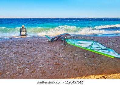 DAHAB, EGYPT - DECEMBER 25, 2017: The windsurfer relax on shore after long training in stormy Aqaba Gulf, on December 25 in Dahab.