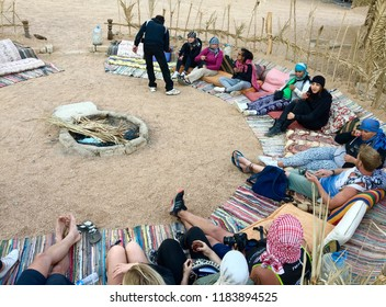 Dahab/ Egypt - January 1 2018: tourists sitting on mats in the desert in a semi circle