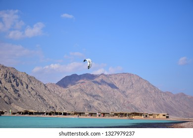 Dahab/Egypt - 30/12/2018 - Kite surfing in Dahab , with mountains in background and clear beach water in sunny day , Blue lagoon , abo ghaloom , three pools