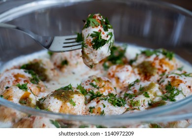 Dahi Vadaor Dahi Bhalla are fried lentil dumplings, topped with curd, sweet and green chutney and spices.