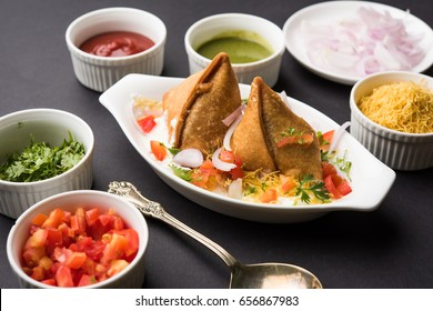Dahi Samosa is a popular tea time junk food or snack served with Curd, sev, onion, mint chutney and tomato ketchup. Served over moody background. Selective focus