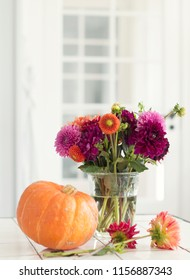 Dahlias in a glass vase with pumpkin
