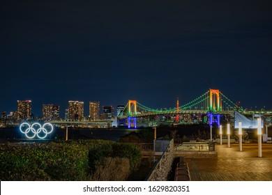 Daiba, Tokyo / Japan - January 24 2020:  Oylmpic rings / symbol illumination light up at Rainbow Bridge - Tokyo Bay, Odaiba Marine Park,   Tokyo Summer Olympics 2020 venue with Tokyo tower background