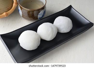 Daifuku japanese desserts black square plate and wood table.