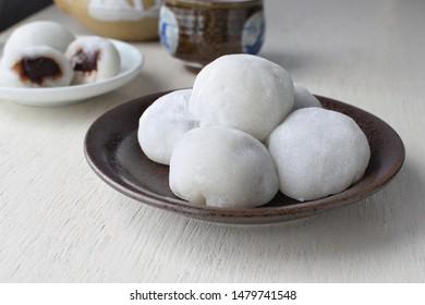 Daifuku japanese desserts on dark brown plate and wood table.