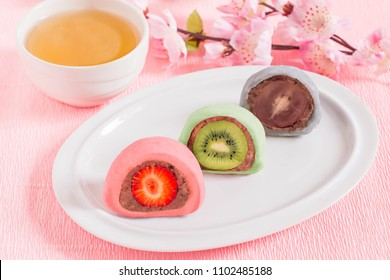 Daifuku mochi stuffed with sweet bean paste and fruits (strawberry, kiwi, grapes) on plate, cup of tea and flowers on pink textured background. Traditional Japanese rice dessert