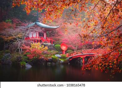 Daigo-ji temple with red kimono woman and umbrella against colorful maple trees in autumn, Kyoto, Japan