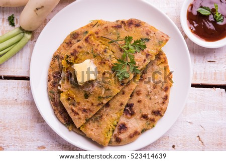 Daikon/Radish or Mooli stuffed Paratha served in a plate with butter and tomato ketchup, over colourful or wooden background. selective focus