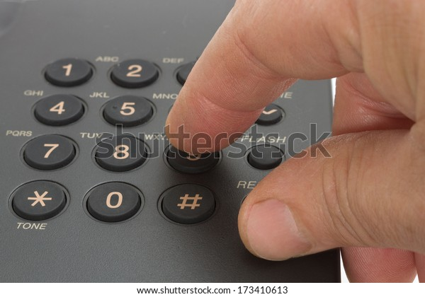Dailing number on a black telephone, with finger pressing on the 9 button