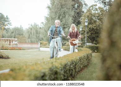 Daily activity. Pleased bearded man keeping smile on his face while riding bicycle in park
