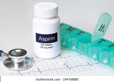 Daily aspirin dose with stethoscope and pill dispenser.
