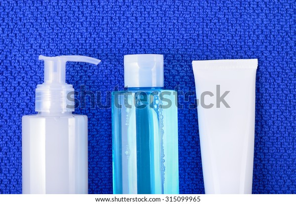 Daily basic care cosmetics - face wash cleansing gel, smoothing toner and cream on navy blue towel. Top view.