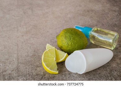 Daily care and hygiene. Roller deodorant, a small bottle with a refreshing face lotion and fresh lime fruit on a gray background.