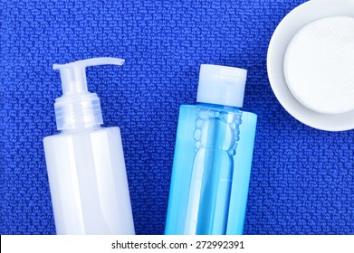 Daily cleansing cosmetics - face wash cleansing gel, smoothing toner and cotton cleansing pads on navy blue towel. Top view.