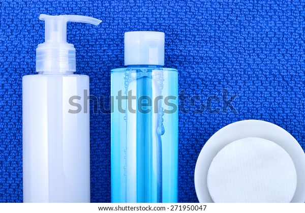 Daily cleansing cosmetics - face wash cleansing gel, smoothing toner and cotton cleansing pads on navy blue towel. Copyspace.