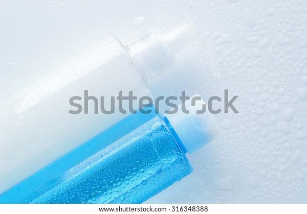 Daily cleansing cosmetics - face wash cleansing gel, smoothing toner with water drops on white background. Copy space.