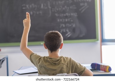 Daily day in a class room at school. Child attending to the lesson on the blackboard