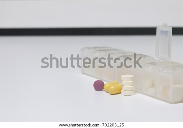 A daily dose of tablets lies near a special container for daily medication. One cell for this day is open, tablets from it lie side by side.