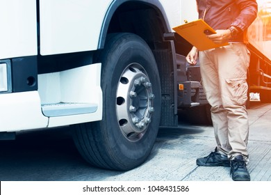 Daily inspection safety, truck driver are  holding a clipboard with inspecting a truck tire.