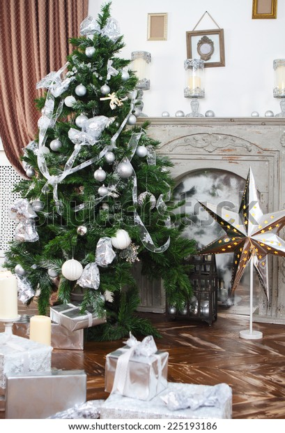 Daily interior in light tones decked out with Christmas tree and fireplace
