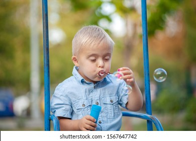 The daily life of a child with disabilities. A boy with Down syndrome blows soap bubbles. Chromosomal and genetic disorder in the baby.