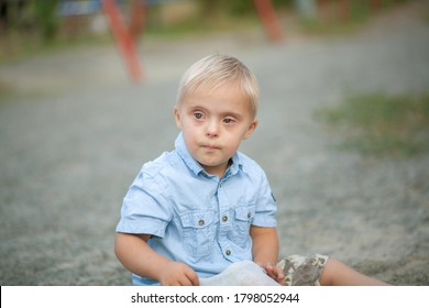 The daily life of a child with disabilities. A boy with Down syndrome sits on the ground and cries. Chromosomal and genetic disorder in the baby.