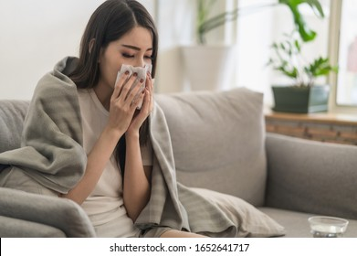 Daily life or health problem concept : Young Asian woman caught a cold and have a running nose or fever have to rest at her home and absent from her job.