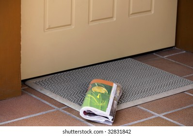 Daily magazine waiting to be picked up outside home entrance door