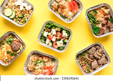 Daily meals in foil boxes on yellow background, top view, flat lay. Healthy food delivery concept. Fitness nutrition for diet.