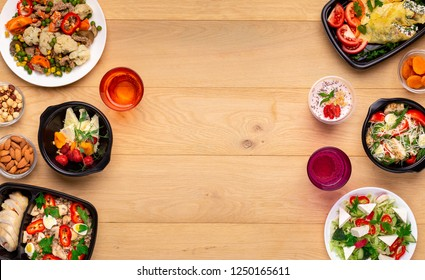 Daily menu for office lunch. Healthy fresh meal in plastic boxes, snacks and drinks on wooden table, top view, mockup, copy space.