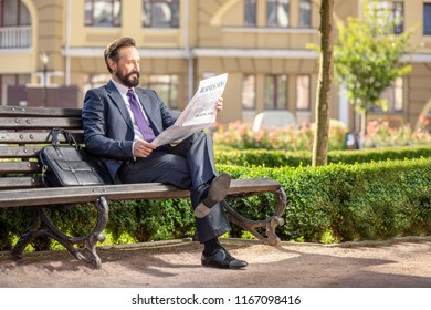 Daily news. Full length of a pleasant smiling businessman reading a newspaper while sitting on the bench