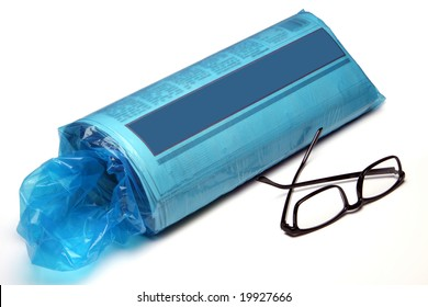 The daily newspaper in the blue plastic bag fresh from the driveway.  The bag is torn and dirty.  The paper shows a blue banner for your own text!  A pair of black reading glasses lies in front.  I