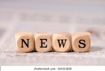 Daily newspaper and small wooden cubes with the word News