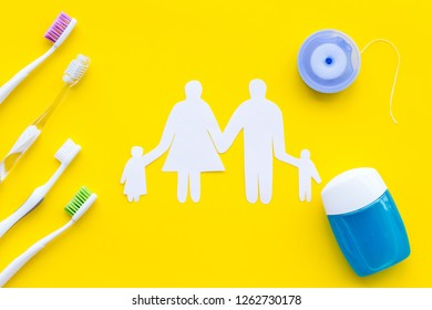 Daily oral hygiene for family. Toothbrush, dental floss and family figures on yellow background top view