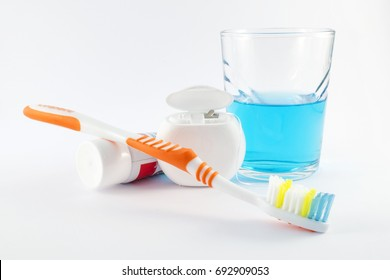 Daily oral hygiene - toothbrush, toothpaste, dental floss and mouthwash on white background