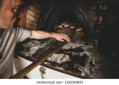 Daily production of bread baked with wood oven with traditional method. Selective Focus