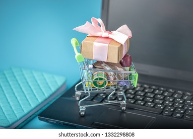 Daily purchases and gifts in the shopping cart on the laptop keyboard on a blue background. The concept of shopping in online stores