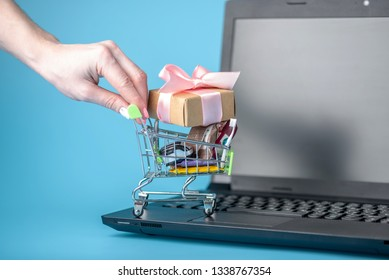 Daily purchases in the shopping cart on the laptop keyboard on a blue background. Online shopping. Hand wheels basket with products