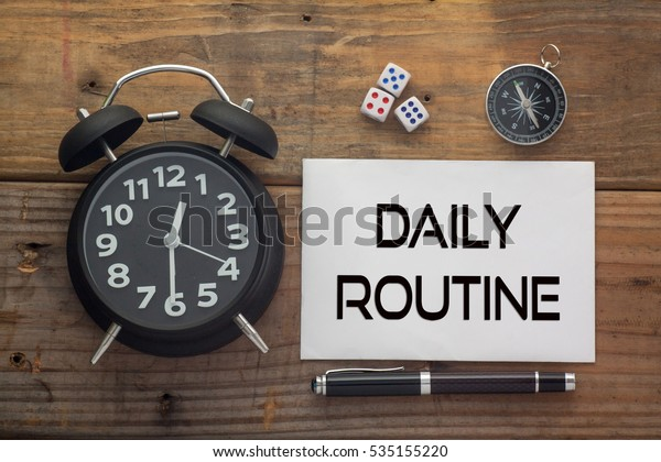 Daily Routine written on paper with wooden background desk,clock,dice,compass and pen.Top view conceptual