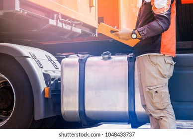 Daily safety inspection, Driver man hand holding clipboard with checking tank of a truck.