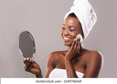 Daily Skincare Routine. Young african american woman with towel on head looking in mirror and cleaning face with cotton pad, grey background with free space
