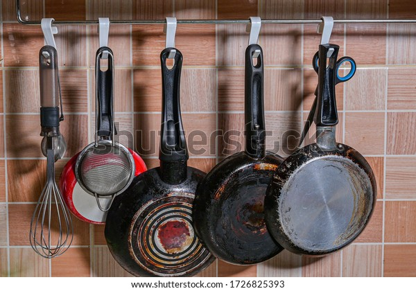 Daily used kitchen ware hanging on tile wall close up view
