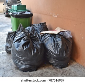 Daily waste are collected and seperated into bag piles of litter, plastic, paper, genernal trashes beside a garbage bin and are waited for a garbage truck