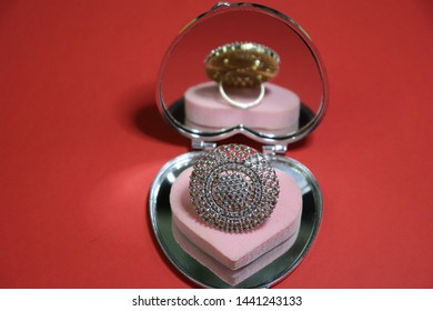 Daimond Ring with reflection on Heart Shape Object isolated on Red Background