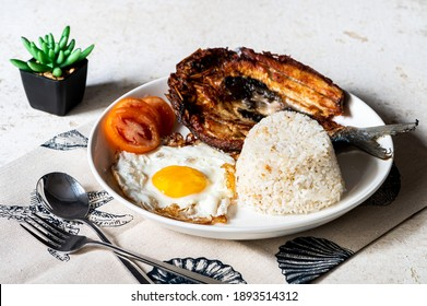 Daingsilog- is a famous Filipino meal can be eaten as breakfast lunch or even dinner and is  composed of boneless fried milkfish, fried egg, and garlic rice.