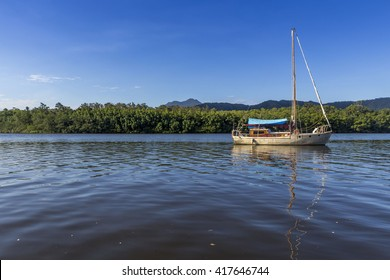 DAINTREE RIVER, CAIRNS, QUEENSLAND, AUSTRALIA: A sailing boat crossing Daintree River at a Crocodile Cruise - a sunny summer evening in January.