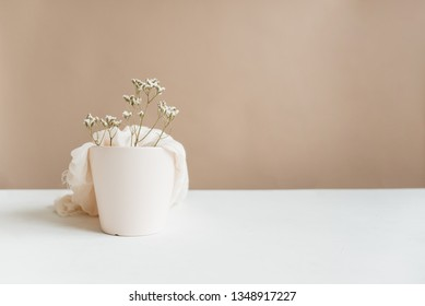 Dainty flowers and soft textures coming out of a light pink planter