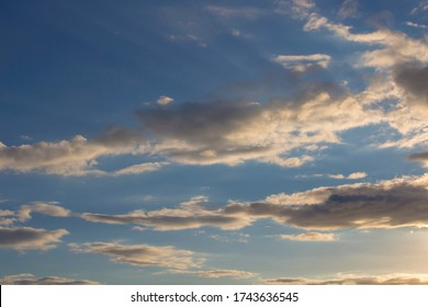 Dainty wispy pale salmon pink and yellow clouds  at sunset in a  blue Australian sky in late autumn add color to the skyscape as evening approaches.