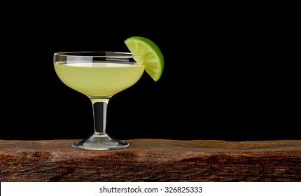 Daiquiri cocktail with lime wedge on wooden table with black background